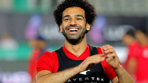Egyptian national team soccer player and Liverpool's star striker Mohammed Salah smiles as he greets fans during the final training of the national team at Cairo Stadium in Cairo, Egypt, Saturday, June 9, 2018. About 2,000 fans gathered at Cairo's main stadium on Saturday to watch Egypt's last home practice before the Pharaohs fly to their World Cup base in Grozny, Chechnya. (AP Photo/Amr Nabil)