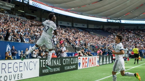 Vancouver Whitecaps' Alphonso Davies, left, and Nicolas Mezquida celebrate Davies' goal against Orlando Cityduring the second half of an MLS soccer match in Vancouver, British Columbia, Saturday June 9, 2018. (Darryl Dyck/The Canadian Press via AP)