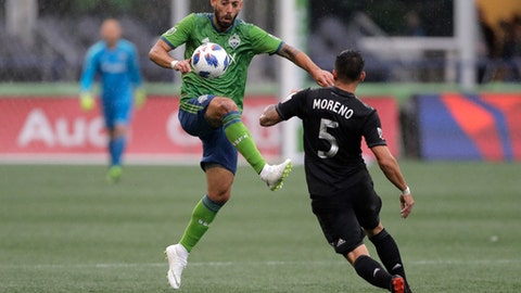 Seattle Sounders midfielder Clint Dempsey, left, kicks the ball away from D.C. United midfielder Junior Moreno (5) during the first half of an MLS soccer match Saturday, June 9, 2018, in Seattle. (AP Photo/Ted S. Warren)
