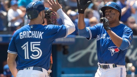 Toronto Blue Jays' Curtis Granderson, right, celebrates with teammate Randal Grichuk after hitting a three run home run against the Baltimore Orioles in the fourth inning of a baseball game in Toronto on Sunday June 10, 2018. (Fred Thornhill/The Canadian Press via AP)