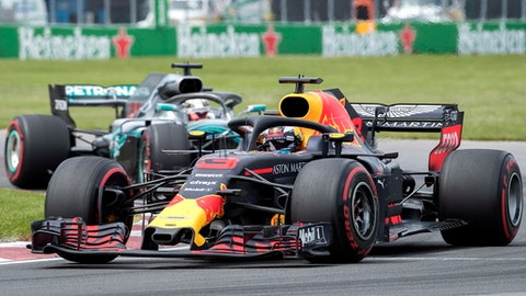 Red Bull Racing driver Daniel Ricciardo, of Australia, takes a turn at the Senna corner ahead of Mercedes driver Lewis Hamilton, of Britain, during the Formula One Canadian Grand Prix auto race in Montreal, Sunday, June 10, 2018, in Montreal. (Graham Hughes/The Canadian Press via AP)