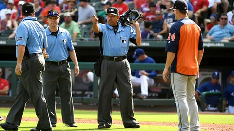 Home plate umpire Alfonso Marquez, center, signals for Houston Astros' George Springer to score after calling a balk on Texas Rangers relief pitcher Keone Kela as Astros manager AJ Hinch looks on during the ninth inning of a baseball game, Sunday, June 10, 2018, in Arlington, Texas. (AP Photo/Jeffrey McWhorter)