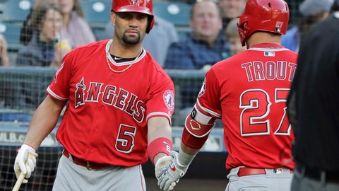 Los Angeles Angels' Albert Pujols, left, greets Mike Trout (27) at the dugout after Trout hit a solo home run against the Seattle Mariners during the first inning of a baseball game, Monday, June 11, 2018, in Seattle. Pujols also hit a solo home run during the first inning. (AP Photo/Ted S. Warren)