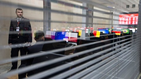 Computer screens showing the national flags of the countries participating in the World Cup 2018 are reflected in a glass-wall as a Russian police officer looks through, at the International Police Cooperation Center opened in Domodedovo, outside Moscow, Russia, Tuesday, June 12, 2018. The top British police officer working at the World Cup in Russia has predicted LGBT fans will follow Russian laws which restrict how they can express their identity in public. (AP Photo/Alexander Zemlianichenko)