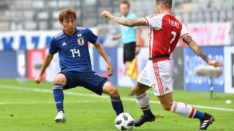 Japan's Takashi Inui, left, and Paraguay's Alan Benitez challenge for the ball during the friendly soccer match between Japan and Paraguay in the Tivoli Stadium in Innsbruck, Austria, on Tuesday, June 12, 2018. (AP Photo/Kerstin Joensson)