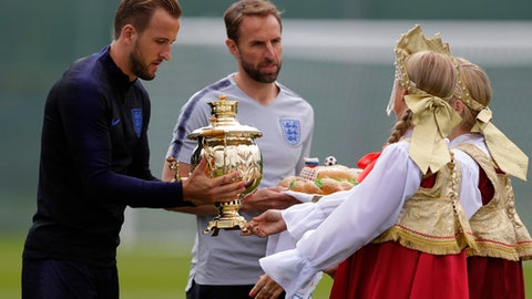 England head coach Gareth Southgate, centre and England's Harry Kane receives a Russian tea urn from a woman in traditional costume before the start of the first training session for the England team at the 2018 soccer World Cup at the Spartak Zelenogorsk stadium, Zelenogorsk near St. Petersburg, Russia, Wednesday, June 13, 2018. (AP Photo/Alastair Grant)