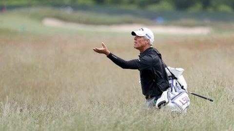 Luis Gagne's caddie turns to catch a ball as he walks through the fescue during a practice round for the U.S. Open Golf Championship, Wednesday, June 13, 2018, in Southampton, N.Y. (AP Photo/Julio Cortez)
