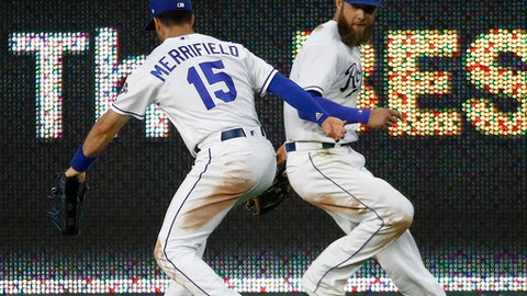 Kansas City Royals center fielder Whit Merrifield (15) and left fielder Alex Gordon chase a double hit by Cincinnati Reds' Jose Peraza during the seventh inning of a baseball game Wednesday, June 13, 2018, in Kansas City, Mo. (AP Photo/Charlie Riedel)