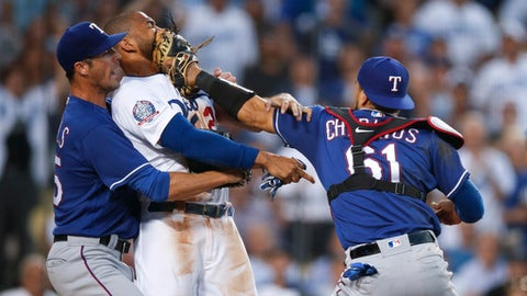 Texas Rangers starting pitcher Cole Hamels, left, restrains Los Angeles Dodgers' Matt Kemp as Kemp scuffles with Rangers catcher Robinson Chirinos during the third inning of a baseball game Wednesday, June 13, 2018, in Los Angeles. (AP Photo/Jae C. Hong)