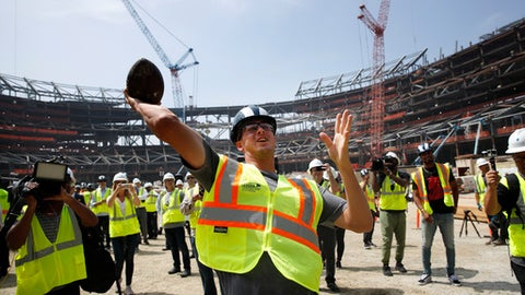 Los Angeles Rams quarterback Jared Goff throws a ball to construction workers while visiting the team's new NFL football stadium Thursday, June 14, 2018, in Inglewood, Calif. Coach Sean McVay scrapped the final practice of minicamp and took his players and coaches on a tour of their multibillion-dollar stadium, which will open for the 2020 season. (AP Photo/Jae C. Hong)