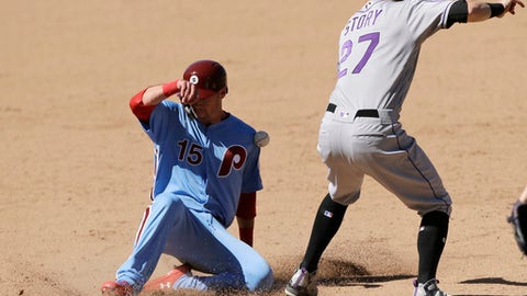 Philadelphia Phillies' Andrew Knapp, left, slides into third base past Colorado Rockies shortstop Trevor Story to advance on a ground out by Scott Kingery during the eighth inning of a baseball game, Thursday, June 14, 2018, in Philadelphia. Philadelphia won 9-3. (AP Photo/Matt Slocum)