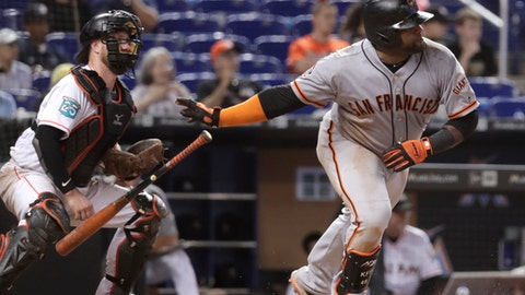 San Francisco Giants' Pablo Sandoval, right, watches after hitting an RBI single to score two runs during the 16th inning of a baseball game against the Miami Marlins, Thursday, June 14, 2018, in Miami. The Giants won 6-3 in 16 innings. At left is Miami Marlins catcher Bryan Holaday. (AP Photo/Lynne Sladky)