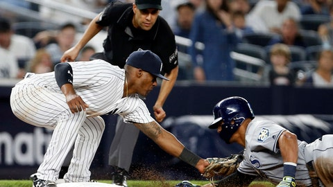 New York Yankees third baseman Miguel Andujar tags out Tampa Bay Rays' Carlos Gomez on an attempted steal of third base during the seventh inning of a baseball game Thursday, June 14, 2018, in New York. Third base umpire Gabe Morales watches the play. (AP Photo/Adam Hunger)