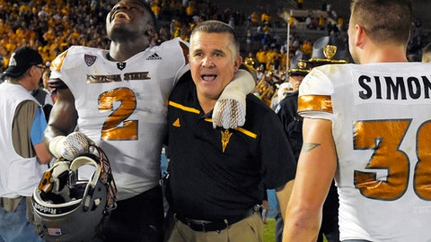 FILE - In this Oct. 3, 2015, file photo, Arizona State linebacker Christian Sam, left, celebrates with head coach Todd Graham, center, and defensive back Jordan Simone after they defeated UCLA 38-23 in an NCAA college football game in Pasadena, Calif. Graham has recruited and coached plenty of fathers during his 17 years in year college football. Married, unmarried. Engaged, estranged. The relationships between player, mother and child have varied and, therefore, so have the ways Graham has tried to help manage those situations. (AP Photo/Mark J. Terrill, File)
