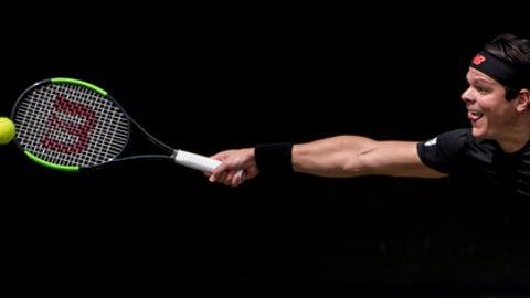 Milos Raonic returns the ball to Tomas Berdych in their quarterfinal match during the ATP Mercedes Cup in Stuttgart, Friday June 15, 2018. (Marijan Murat/dpa via AP)