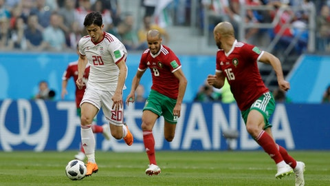 Iran's Sardar Azmoun, left, and Morocco's Noureddine Amrabat, right, compete for the ball during the group B match between Morocco and Iran at the 2018 soccer World Cup in the St. Petersburg Stadium in St. Petersburg, Russia, Friday, June 15, 2018. (AP Photo/Andrew Medichini)