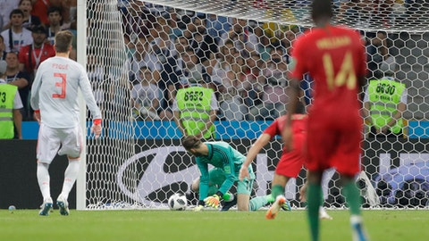 Spain goalkeeper David De Gea looks round as he fails to save a goal by Portugal's Cristiano Ronaldo, unseen, during the group B match between Portugal and Spain at the 2018 soccer World Cup in the Fisht Stadium in Sochi, Russia, Friday, June 15, 2018. (AP Photo/Sergei Grits)