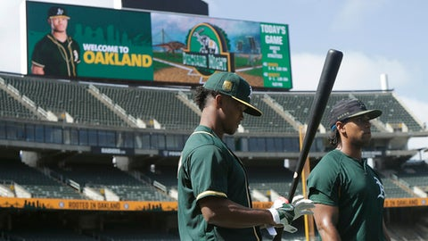 Oakland Athletics' Kyler Murray, left, waits to hit during batting practice next to left fielder Khris Davis, right, before a baseball game against the Los Angeles Angels in Oakland, Calif., Friday, June 15, 2018. (AP Photo/Jeff Chiu)