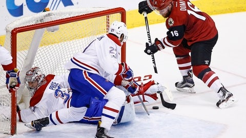 Arizona Coyotes left wing Max Domi (16) gets ready to send the puck past Montreal Canadiens center Alex Galchenyuk (27) and goalie Carey Price, left, for a goal during the second period of an NHL hockey game Thursday, Feb. 9, 2017, in Glendale, Ariz. (AP Photo/Ross D. Franklin)