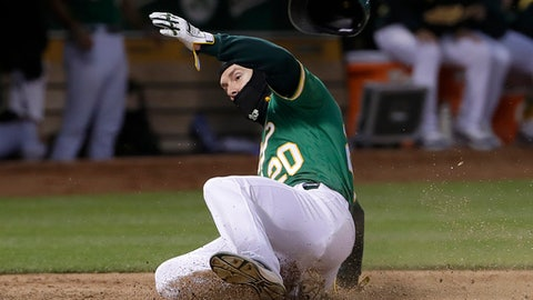 Oakland Athletics' Mark Canha scores against the Los Angeles Angels during the fifth inning of a baseball game in Oakland, Calif., Friday, June 15, 2018. (AP Photo/Jeff Chiu)