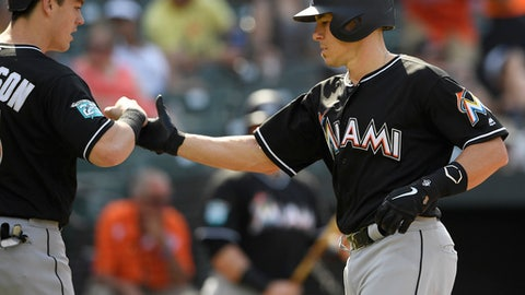 Miami Marlins' J.T. Realmuto, right, celebrates his two-run home run with Brian Anderson, left, during the third inning of a baseball game against the Baltimore Orioles, Saturday, June 16, 2018, in Baltimore. (AP Photo/Nick Wass)