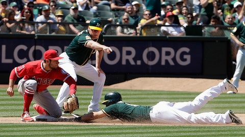 Oakland Athletics' Chad Pinder, bottom, slides into third base with a triple as Los Angeles Angels' David Fletcher, left, and Athletics third base coach Matt Williams look on during the seventh inning of a baseball game in Oakland, Calif., Saturday, June 16, 2018. (AP Photo/Jeff Chiu)