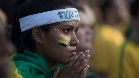 A Brazilian soccer fan reacts as she watches a live telecast of her team's World Cup match against Switzerland in Rio de Janeiro, Brazil, Sunday, June 17, 2018. (AP Photo/Leo Correa)
