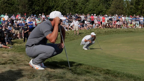 Brooks Koepka and Dustin Johnson line up their putts on the 12th green during the final round of the U.S. Open Golf Championship, Sunday, June 17, 2018, in Southampton, N.Y. (AP Photo/Julio Cortez)