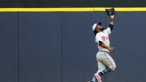 Philadelphia Phillies' Odubel Herrera makes a leaping catch at the wall during the ninth inning of a baseball game against the Milwaukee Brewers, Sunday, June 17, 2018, in Milwaukee. The Phillies won 10-9. (AP Photo/Aaron Gash)