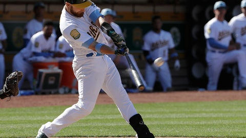 Oakland Athletics' Jonathan Lucroy hits an RBI-single to drive in the winning run during the eleventh inning of a baseball game against the Los Angeles Angels in Oakland, Calif., Sunday, June 17, 2018. (AP Photo/Jeff Chiu)