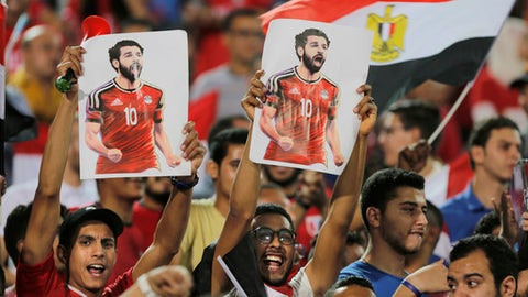 FILE - In this file photo from June 9, 2018, Egypt fans hold poster of striker Mohammed Salah during the team's final training session in Cairo before the World Cup. (AP Photo/Amr Nabil, File)