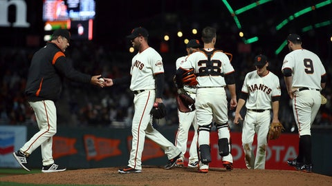 San Francisco Giants manager Bruce Bochy, left, relieves pitcher Hunter Strickland in the ninth inning of a baseball game against the Miami Marlins Monday, June 18, 2018, in San Francisco. (AP Photo/Ben Margot)