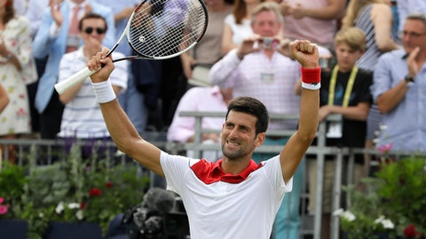 Novak Djokovic of Serbia celebrates winning his singles tennis match against John Millman of Australia at the Queen's Club tennis tournament in London, Tuesday, June 19, 2018. (AP Photo/Kirsty Wigglesworth)