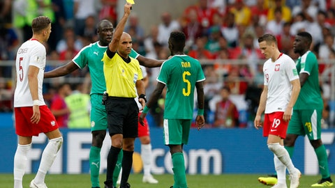 Referee Nawaf Shukralla from Bahrain, center, shows a yellow card to Senegal's Idrissa Gana Gueye during the group H match between Poland and Senegal at the 2018 soccer World Cup in the Spartak Stadium in Moscow, Russia, Tuesday, June 19, 2018. (AP Photo/Eduardo Verdugo)