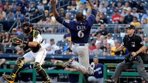 Milwaukee Brewers' Lorenzo Cain (6) begins his slide to score on a double by Jesus Aguilar off Pittsburgh Pirates starting pitcher Jameson Taillon as catcher Francisco Cervelli waits for the late throw and umpire David Rackley, right, watches during the third inning of a baseball game in Pittsburgh, Tuesday, June 19, 2018. (AP Photo/Gene J. Puskar)