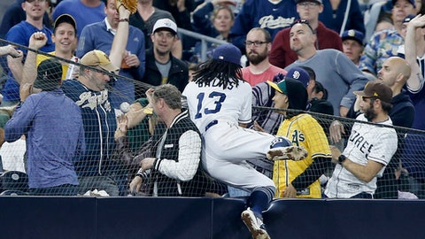 San Diego Padres shortstop Freddy Galvis leaps out but cannot reach over the fence to catch a fly ball that went into the stands hit by Oakland Athletics' Matt Olson during the fourth inning of a baseball game in San Diego, Tuesday, June 19, 2018. (AP Photo/Alex Gallardo)