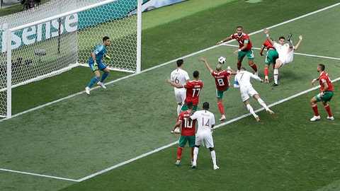 Portugal's Cristiano Ronaldo, with blue captain's armband, heads the ball to score the opening goal during the group B match between Portugal and Morocco at the 2018 soccer World Cup in the Luzhniki Stadium in Moscow, Russia, Wednesday, June 20, 2018. (AP Photo/Victor Caivano)