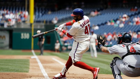 Philadelphia Phillies' Carlos Santana hits an RBI-sacrifice fly off St. Louis Cardinals starting pitcher Michael Wacha during the first inning of a baseball game, Wednesday, June 20, 2018, in Philadelphia. At right is Cardinals catcher Yadier Molina. (AP Photo/Matt Slocum)