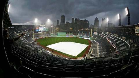 A young baseball fan in the last row of the upper deck at PNC Park waits out a downpour during a delay of the start of a baseball game between the Pittsburgh Pirates and the Milwaukee Brewers in Pittsburgh, Wednesday, June 20, 2018. (AP Photo/Gene J. Puskar)