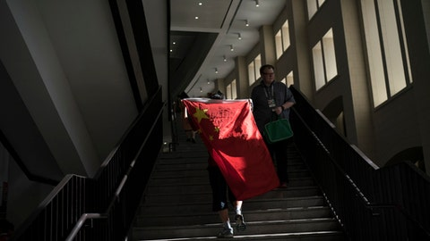 FILE - In this Wednesday, June 20, 2018 file photo, a soccer fan from China carries his national flag as the walks inside the Luzhniki Stadium during the group B match between Portugal and Morocco at the 2018 soccer World Cup in Moscow, Russia. Chinese sponsors are more visible than ever and tens of thousands of Chinese fans have descended on Moscow, using their growing economic clout to secure top-dollar seats and dreaming of the day, perhaps not that far off, when China will host football's showcase. (AP Photo/Felipe Dana)