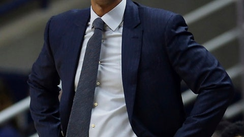 FILE - In this Feb. 7, 2018, file photo, then-Connecticut head coach Kevin Ollie watches the first half an NCAA college basketball game, in Storrs, Conn. The University of Connecticut says it fired men's basketball coach Kevin Ollie after finding NCAA violations that included improper workouts and improper contact with recruits by Ollie and former UConn star Ray Allen. In a statement to The Associated Press on Thursday, June 21, 2018, Ollie's lawyer Jacques Parenteau called the infractions cited by UConn in firing Ollie minimal and isolated. He also says they fail to justify withholding the more than $10 million they believe Ollie is owed under his contract. (AP Photo/Jessica Hill, File)