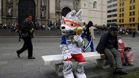 A man dressed like World Cup mascot Zabivaka holds a replica world cup trophy, as he sits on a bench prior the group C match between France and Peru at the 2018 soccer World Cup, in Lima, Peru, Thursday, June 21, 2018.(AP Photo/Martin Mejia)