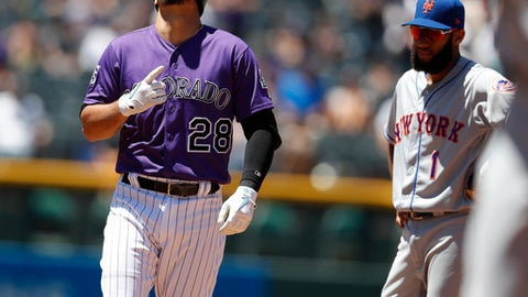 Colorado Rockies' Nolan Arenado, left, gestures as he reaches second base after hitting a double to drive in two runs as New York Mets shortstop Amed Rosario looks on in the second inning of a baseball game Thursday, June 21, 2018, in Denver. (AP Photo/David Zalubowski)