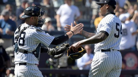 New York Yankees closer Aroldis Chapman (54) celebrates with catcher Austin Romine (28) after Chapman got the save after the Yankees defeated the Seattle Mariners 4-3 in a baseball game Thursday, June 21, 2018, at Yankee Stadium in New York. (AP Photo/Bill Kostroun)