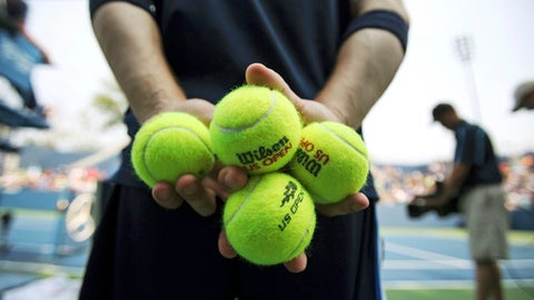FILE - In this Sept. 3, 2015, file photo, a ballperson holds balls for play during the second round of the U.S. Open tennis tournament in New York. Look for ballpersons rolling, not throwing, balls on court at the U.S. Open. The U.S. Tennis Association says it will drop the throw to broaden the pool of applicants for ballperson tryouts.  (AP Photo/Adam Hunger, File)