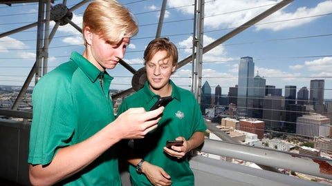Rasmus Dahlin, left, and Adam Boqvist, both of Sweden, share photos on social media in Dallas, Thursday, June 21, 2018. The NHL hockey draft takes place Friday and Saturday in Dallas. (AP Photo/Michael Ainsworth)