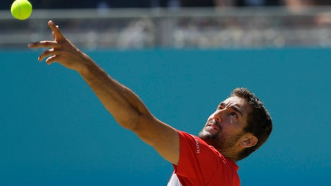 Marin Cilic of Croatia serves to Sam Querrey of the USA during their quarterfinal tennis match at the Queen's Club tennis tournament in London, Friday, June 22, 2018. (AP Photo/Kirsty Wigglesworth)