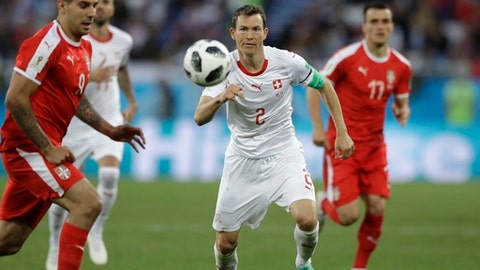 Switzerland's Stephan Lichtsteiner, centre, follows the ball during the group E match between Switzerland and Serbia at the 2018 soccer World Cup in the Kaliningrad Stadium in Kaliningrad, Russia, Friday, June 22, 2018. (AP Photo/Matthias Schrader)