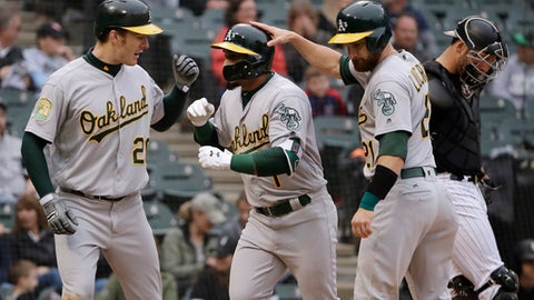 Oakland Athletics' Franklin Barreto, center, celebrates with Mark Canha, left, and Jonathan Lucroy after hitting a three-run home run against the Chicago White Sox during the eighth inning of the first game of a baseball doubleheader in Chicago, Friday, June 22, 2018. (AP Photo/Nam Y. Huh)