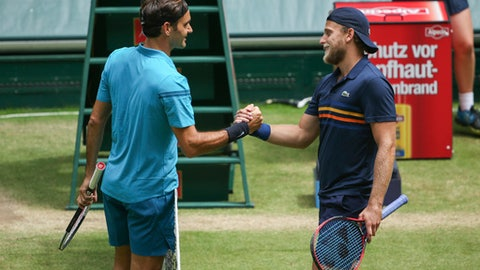 Roger Federer, left, greets Denis Kudla, right, after winning their semi final match at the Gerry Weber Open ATP tennis tournament in Halle, Germany, Saturday, June 23, 2018. (Friso Gentsch/dpa via AP)